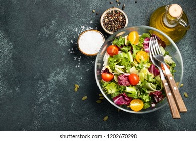 Healthy vegetable salad of fresh tomato, cucumber, onion, spinach, lettuce and pumpkin seeds in bowl. Diet menu. Top view with copy space