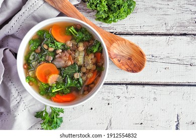 Healthy vegetable soup with kale and lentils. Overhead view table scene on a rustic white wood background.