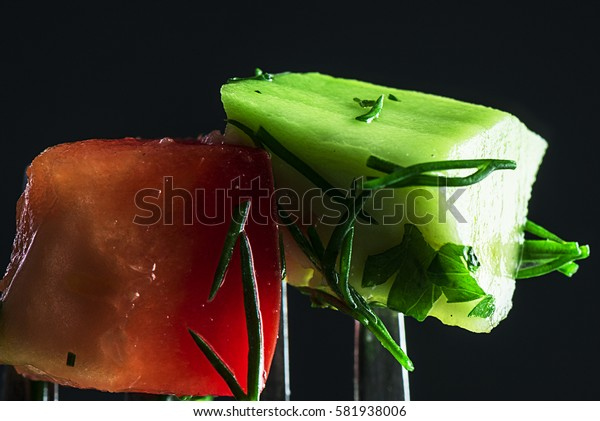Healthy vegetables on a fork, close-up. Dark background. Focus on vegetables