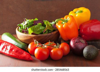 healthy vegetables pepper tomato salad onion avocado on rustic background