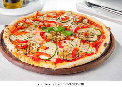 Healthy vegetables vegetarian pizza with grilled zucchini and eggplant slices on the served table. Selective focus