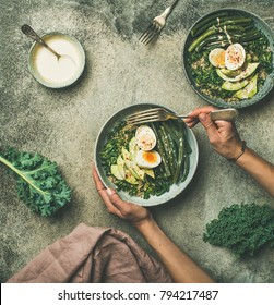 Healthy vegetarian breakfast bowls flat-lay. Quinoa, kale, beans, avocado, egg with tahini dressing bowls over grey concrete background, top view. Energy boosting, clean eating, diet food concept