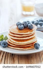 Healthy vegetarian breakfast or brunch, favorite meal. Homemade pancakes, fresh summer berries, coffee and juice on wooden table