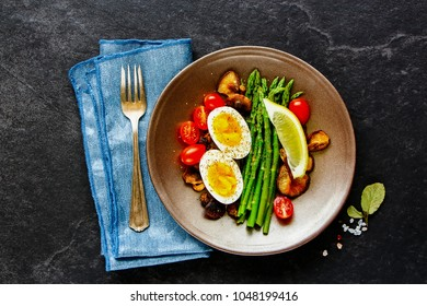 Healthy vegetarian breakfast plate with aspargus, tomatoes, mushrooms and eggs over black stone copy space background. Energy boosting food concept. Top view. Flat lay