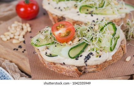 Healthy vegetarian bruschettas with bread, micro greens, hummus, cherry tomatoes, cucumbers and pine nuts on rustic wooden table. Healthy lifestyle and eating right concept. Close up