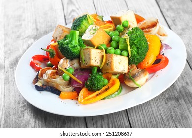Healthy vegetarian cuisine with a tofu salad with colorful roast vegetables including sweet peppers, onion and mushrooms, peas and broccoli