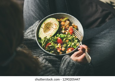 Healthy vegetarian dinner. Woman in jeans and woolen sweater holding bowl with fresh salad, avocado half, grains, beans, roasted vegetables, top view. Superfood, clean eating, dieting food concept