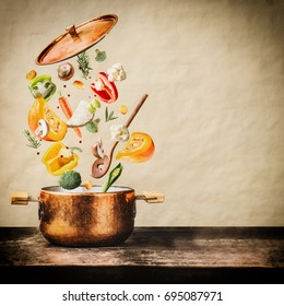Healthy vegetarian eating and cooking with various flying chopped vegetables ingredients, cooking pot and  spoon at wooden table at natural background, front view. Clean food concept