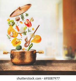 Healthy vegetarian eating and cooking with various flying chopped vegetables ingredients, cooking pot and  spoon at table desk at kitchen background, front view. Clean food concept