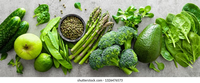 Healthy vegetarian food concept background, fresh green food selection for detox diet, raw broccoli, apple, cucumber, spinach, peas, asparagus, avocado, lime, corn salad and mung bean, top view