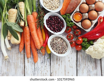 Healthy vegetarian food concept ingredients. Set of fresh seasonal vegetables and various of super food products over old wooden table. Overhead view