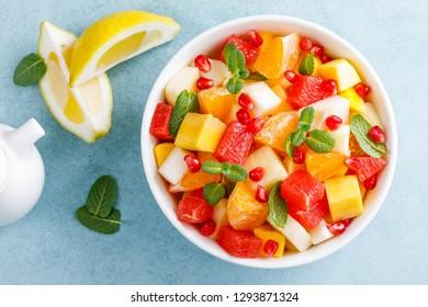 Healthy vegetarian fresh fruit salad with apple, pear, tangerine, grapefruit, mango, pomegranate and lemon juice