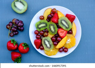Healthy Vegetarian Fresh Fruit Summer Salad Dessert With Oranges, Strawberries, Kiwi Fruit Peaches And Grapes, On A Blue Background