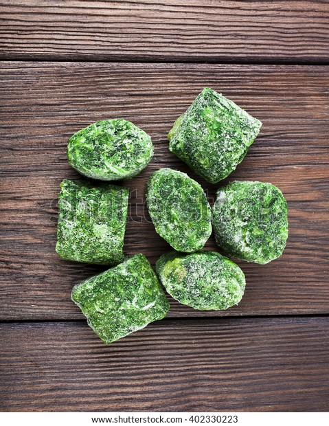 Healthy vegetarian frozen spinach on old wooden background