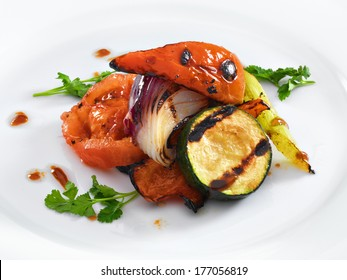Healthy vegetarian grilled vegetables served on a white round plate. Isolated on white.