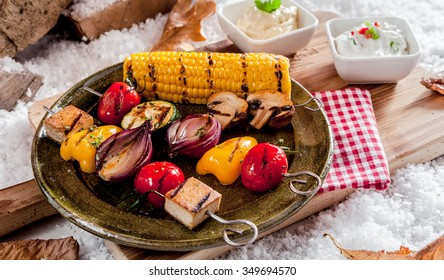 Healthy vegetarian kebabs with grilled pepper, onion, eggplant, bean curd and corn on the cob served on a rustic pewter plate outdoors in snow