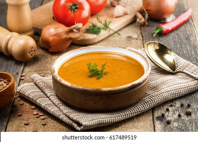 Healthy vegetarian lentil soup in a rustic clay bowl on an old wooden table. Delicious healthy meal served on a canvas tablecloth. Close-up shot.