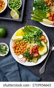 Healthy vegetarian lunch bowl with avocado, chickpeas, quinoa and vegetables, garnished with microgreens and nut dressing. Flat lay on dark concrete background.