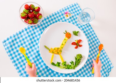 Healthy vegetarian lunch for little kids, vegetables and fruit served as animals, corn, broccoli, carrots and fresh strawberry helping to learn eating right and clean, child's hands holding spoon