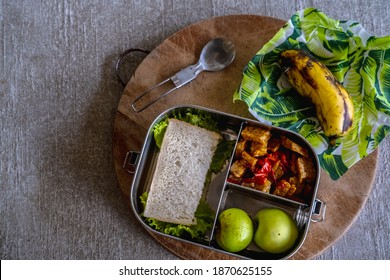 Healthy vegetarian meal served in eco-friendly kitchen tableware: stainless metal food container or lunch box, beeswax wraps with spork on wooden board. Zero waste sustainable plastic free lifestyle