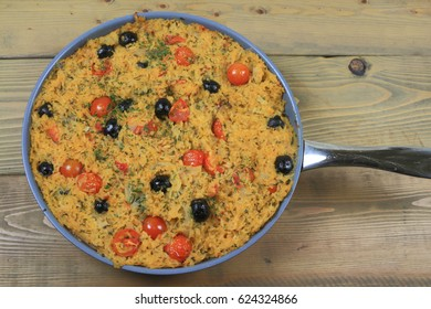Healthy Vegetarian Mediterranean Style meal of rice, onion, small cherry tomatoes (cut in half and whole) and black olives, seasoned with parsley flakes and red pepper, baked in a pot
