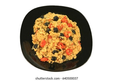 Healthy Vegetarian Mediterranean Style meal of rice, onion, small cherry tomatoes (cut in half and whole), black olives, seasoned with parsley flakes and red pepper, served on a black porcelain dish