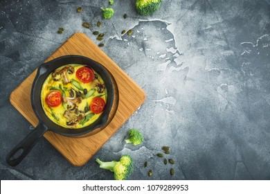 Healthy vegetarian omelet in frying pan and pumpkin seeds. Flat lay, top view