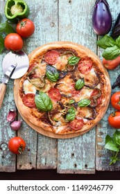 Healthy vegetarian pizza. Aubergine pizza with tomato, bell pepper and basil surrounded with raw ingredients on old shabby blue boards copyspace