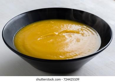 healthy vegetarian pumpkin cream soup in black bowl