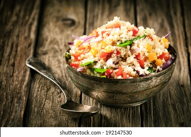 Healthy vegetarian quinoa recipe with colourful bell pepper, tomato, onion and fresh herbs in a rustic metal bowl on an old wooden kitchen counter