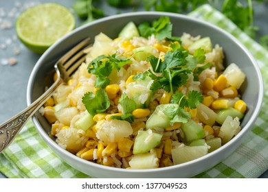 Healthy vegetarian salad with brown rice, corn, cucumber, pineapple and coriander.