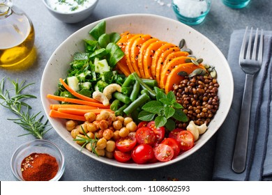 Healthy vegetarian salad. Buddha bowl. Lentil. chickpea, carrot, pumpkin, tomatoes, cucumber, lettuce. Close up.