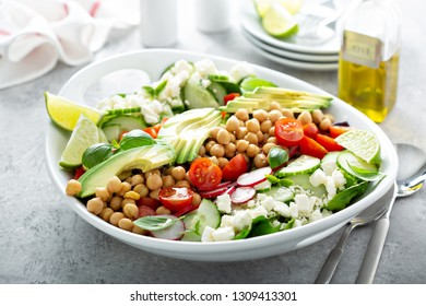 Healthy vegetarian salad with chickpeas, fresh vegetables, avocado and feta