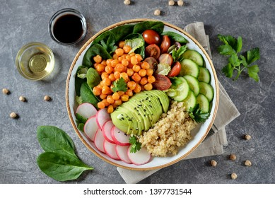 Healthy vegetarian salad with chickpeas, quinoa, cherry tomatoes, cucumber, radish, spinach, avocado and parsley. Ketogenic diet. Top view.