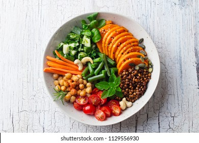 Healthy vegetarian salad. Lentil, chickpea, carrot, pumpkin, tomatoes, cucumber, lettuce. Wooden background. Top view.