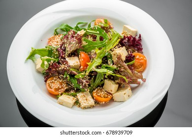 Healthy vegetarian salad and spicy soy cheese tofu with paprika and basil