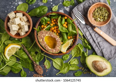 Healthy vegetarian salad with tofu, chickpeas, avocado and sunflower seeds. Healthy vegan food concept. Dark background, top view, copy space.