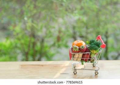 healthy vegetarian shopping cart for green, healthy and clean food shopping concept. Shopping trolley full of vegetables and fruits on brown table over blurred green background