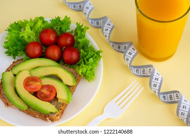 Healthy vegetarian snack with avocado, cherry tomatoes, lettuce leaves, glass of juice, measuring tape. Top view. Diet or weight control concept.