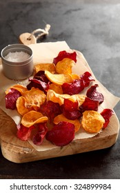 Healthy vegetarian snack of crisp crunchy fried or oven-baked beetroot chips served with rock or sea salt on a wooden chopping board , close up high angle view with copyspace behind