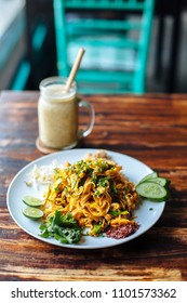 Healthy Vegetarian vegan menu Padthai noodle with smoke tofu and mixed vegetable - wheat germs,lime,cucumber,parsley and banana smoothies