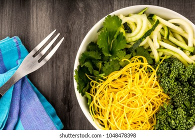 Healthy Vegetarian Or Vegan Noodle Buddha Bowl With Courgettes Broccoli And Coriander On A Dark Wooden Kitchen Table Top
