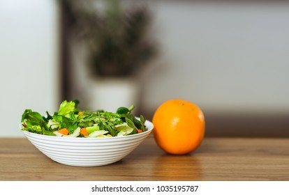 Healthy Vegetarian Vegetable Salad and an orange on table