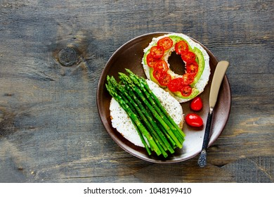 Healthy veggie breakfast flat lay. Sandwiches with soft cheese, avocado, tomatoes and aspargus on bagels over wooden background. Top view. Weight loss, clean eating, detox food concept