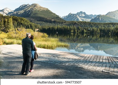 healthy and vital senior couple standing at lake in austrian alps with beautiful mountain view
