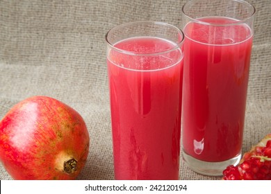 Healthy vitamin beverage: fresh made pomegranate juice. Pomegranate in the background