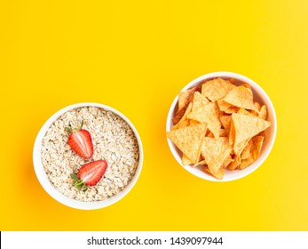 Healthy vs unhealthy food and dieting concept. Fried chips or nachos and oat flakes with strawberries in bowls isolated on yellow color studio background with copy space. Flat lay, view from top.