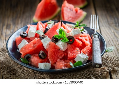 Healthy watermelon salad with feta, olives and mint leaves