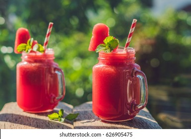 Healthy watermelon smoothie in Mason jars with mint and striped straws against the background of greenery.