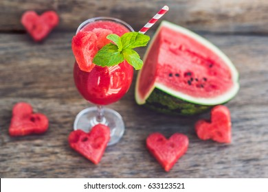 Healthy watermelon smoothie with mint, a piece of watermelon, hearts and a striped straw on a wood background.
